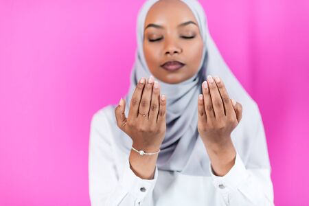 Modern African Muslim woman makes traditional prayer to God, keeps hands in praying gesture, wears traditional white clothes, has serious facial expression, isolated over plastic pink  background