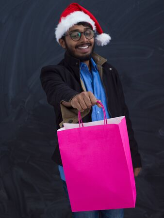 Indian  man wearing party clothes in Santa hat with shopping bag on dark  background studio dark skinned middle eastern Santa Claus merry Christmas Stock Photo