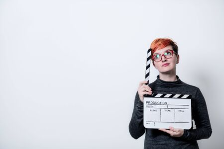 redhead woman on white background holding movie clapper cinema concept