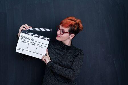 redhead woman on black chalkboard holding movie clapper cinema concept