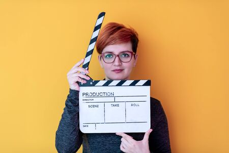 redhead woman holding movie clapper against yellow background cinema concept