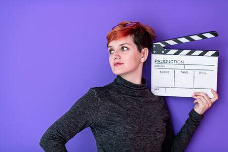 redhead woman holding movie clapper against purple background cinema concept