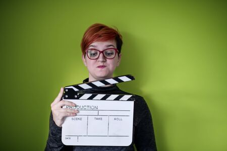 redhead woman holding movie clapper isolated against green background cinema concept in studio
