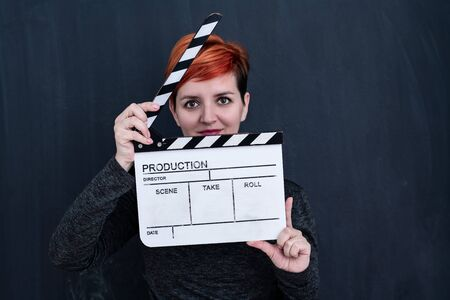 redhead woman on black chalkboard holding movie clapper cinema concept