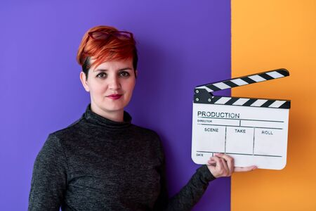 redhead woman holding movie clapper against colorful background cinema concept