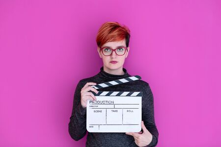 redhead woman holding movie clapper isolated against pink background cinema concept in studio Banco de Imagens