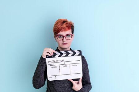 redhead woman holding movie clapper against cyan background cinema concept Banco de Imagens