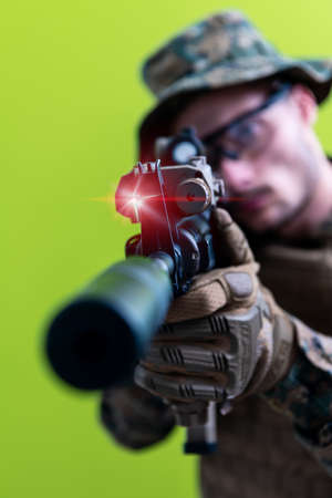 modern warfare american marines soldier in action while sneaking and aiming  sniper riffle on laseer sight optics  in combat position and  searching for target in battle green background
