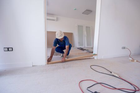 male workers carpenters installing interior glass door with a wooden frame at new luxury apartment Reklamní fotografie