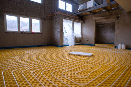 yellow underfloor heating installation with white polyethylene pipes on construction site of new two level apartment