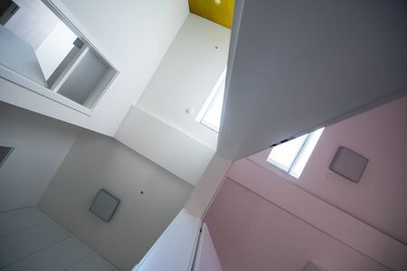 looking up on ceiling with halogen spots lamps and roof windows in apartment or house. Stretch ceiling white and complex shape