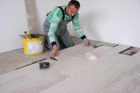 skilled worker installing the ceramic wood effect tiles on the floor Worker making laminate flooring on the construction site of the new apartment Imagens