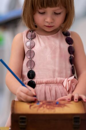 beautiful cute little girl in pink dress painting jewelry box while having fun at home