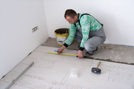 skilled worker installing the ceramic wood effect tiles on the floor Worker making laminate flooring on the construction site of the new apartment Standard-Bild