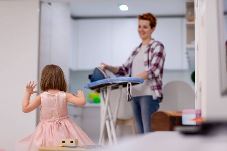 happy family having fun together at home  cute little daughter in a pink dress playing and dancing while young redhead mother ironing clothes behind her Archivio Fotografico