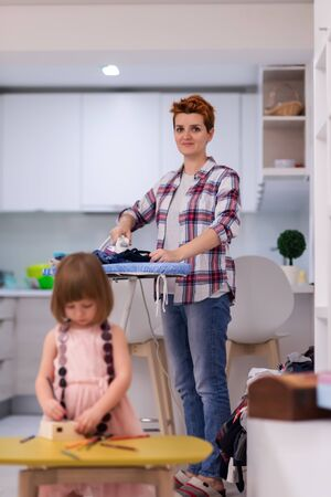 happy family spending time together at home  cute little daughter in a pink dress playing and painting the jewelry box while young redhead mother ironing clothes behind her