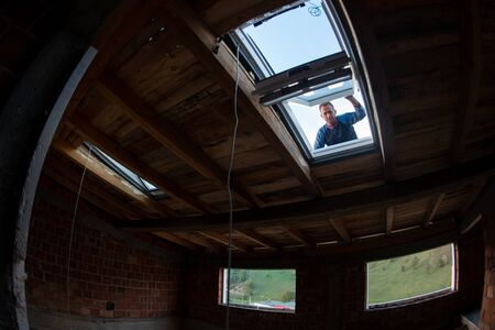 construction worker installing environmentally friendly and energy efficient roof window. Room under construction with wooden beams, boards and windows view from inside Imagens