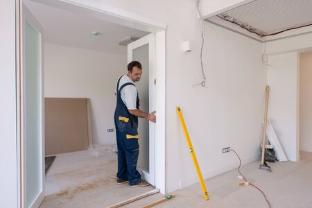 male workers carpenters installing interior glass door with a wooden frame at new luxury apartment Imagens