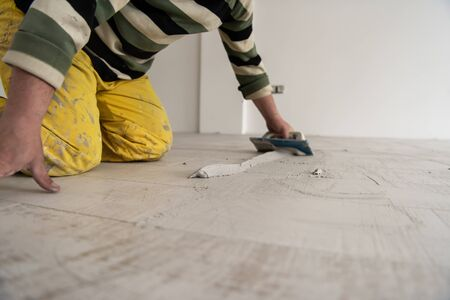 Grouting ceramic tiles. Tilers filling the space between ceramic wood effect tiles using a rubber trowel on the floor in new modern apartment Imagens