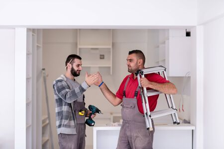 two professional workers giving high five to each other during installation a new stylish modern kitchen furniture