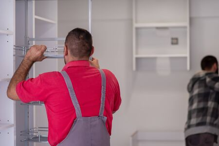 two professional workers installing a new stylish modern kitchen furniture