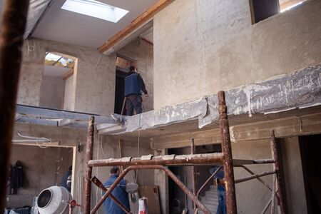 workers on construction site interior of new two levels apartment with windows and red brick walls  construction site in progress to new house Imagens