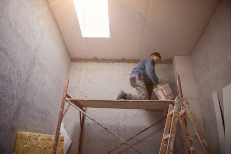 young professional construction worker using scaffold while plastering on gypsum ceiling inside the new big modern two levels apartment