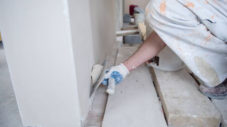 young professional construction worker plastering on gypsum walls inside the new big modern two levels apartment Imagens