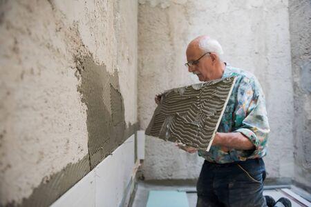 experienced senior construction worker installing big ceramic tiles on interior concrete walls