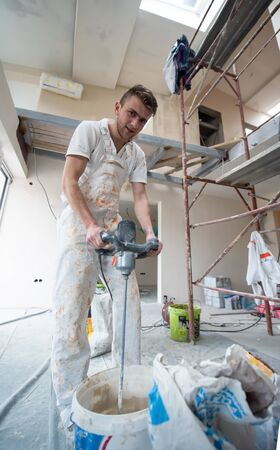professional Male builder mixing plaster in bucket using electric mixer at new unfinished apartment