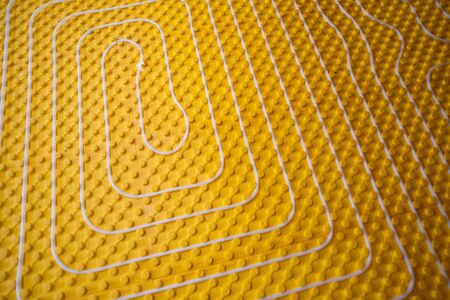yellow underfloor heating installation with white polyethylene pipes on construction site of new two level apartment Archivio Fotografico