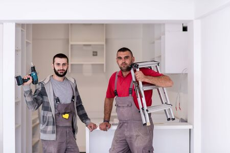portrait of two professional workers during installation a new stylish modern kitchen furniture
