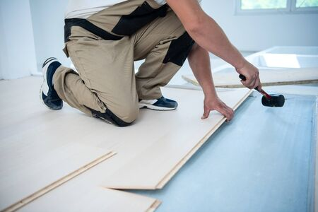 professional carpenter using rubber hammer while installing new laminated wooden floor in a unfinished apartment