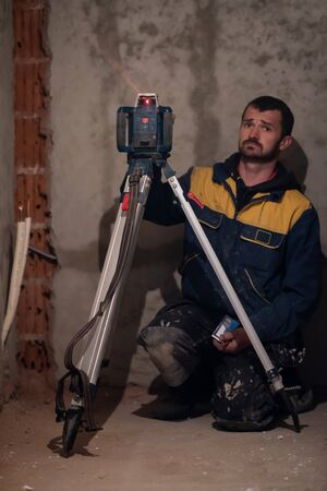 professional worker using laser level in a building under construction. Laser equipment at a construction site