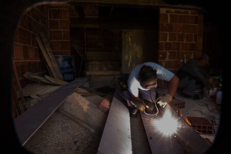 welder with protective mask welding steel structures and bright sparks in construction industry 写真素材