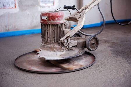 professional machine for performing and polishing sand and cement screed floor on the construction site of a new two-level apartment. Sand and cement floor screed