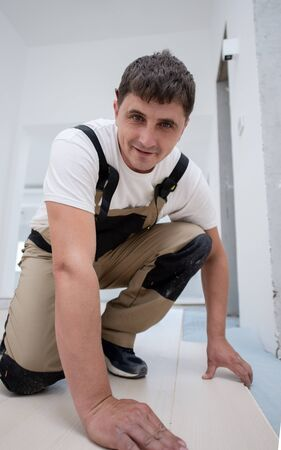 professional carpenter installing new laminated wooden floor in a unfinished apartment