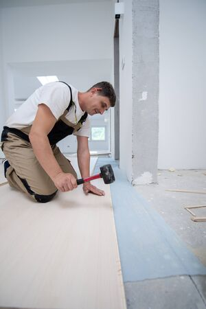 professional carpenter using rubber hammer while installing new laminated wooden floor in a unfinished apartment 版權商用圖片
