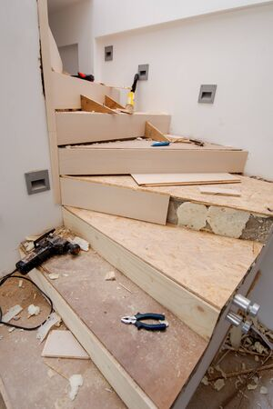 work in progress on stylish interior with wooden stairs in big modern two level luxury apartment Banque d'images - 143471407
