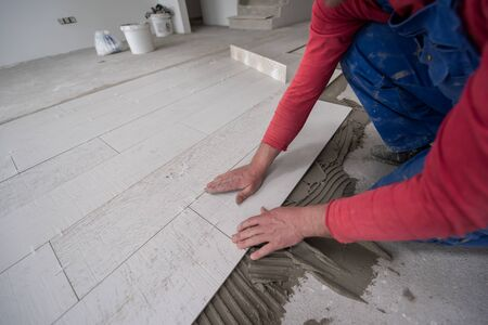 skilled worker installing the ceramic wood effect tiles on the floor Worker making laminate flooring on the construction site of the new apartment Zdjęcie Seryjne