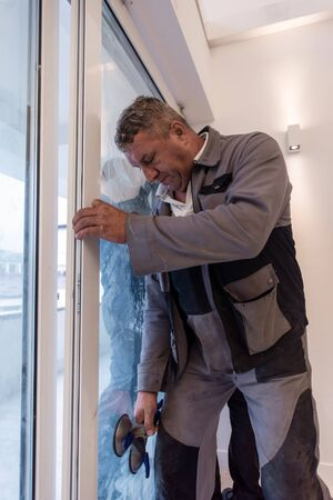 professional carpenters installing a balcony door in a new apartment with panoramic windows