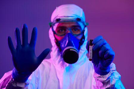 Coronavirus, Doctor holding positive covid-19 virus Blood Sample test tube. Wearing biohazard epidemic Protective mask, suit and glows neon light background Foto de archivo