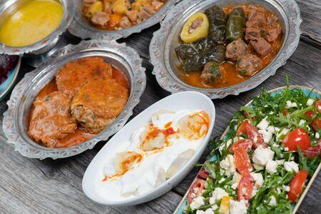 Eid Mubarak Traditional Ramadan Iftar dinner. Assorted tasty food in authentic rustic dishes on wooden blue background.  Turkish Bosnian food meat kebab, pita, Sarma, klepe, sogan dolma,  fried meatballs. Middle eastern dates.  Turkish cuisine. Top view. Eastern food