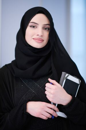 young modern muslim business woman holding tablet computer wearing hijab clothes at home Stock Photo