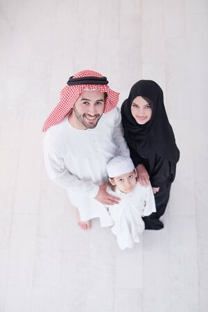 top view portrait of young happy arabian muslim family couple with son in traditional clothes spending time together during the month of Ramadan at home Archivio Fotografico