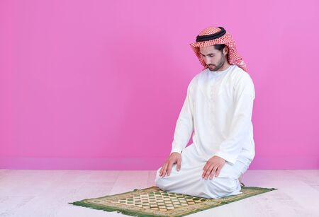 young arabian muslim man in traditional clothes praying on the carpet in front of pink wall before iftar dinner during a ramadan feast at home