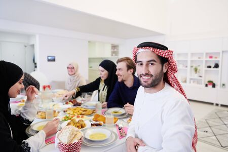 young arabian man having Iftar dinner with muslim family Eating traditional food during Ramadan feasting month at home. The Islamic Halal Eating and Drinking Islamic family