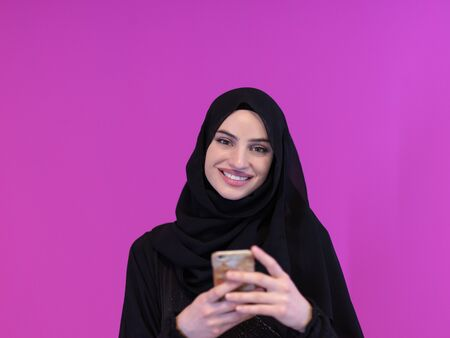 young modern muslim business woman using smartphone wearing hijab clothes isolated on pink background Standard-Bild