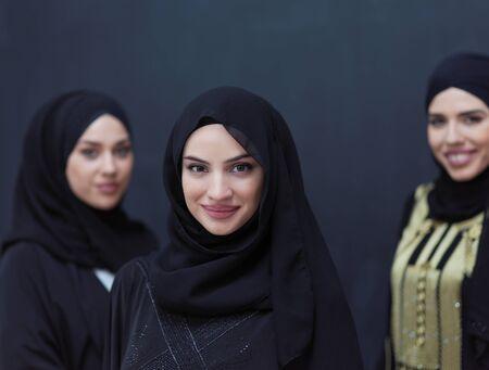 group portrait of beautiful muslim women in fashionable dress with hijab isolated on black chalkboard background representing modern islam fashion and ramadan kareem concept Archivio Fotografico