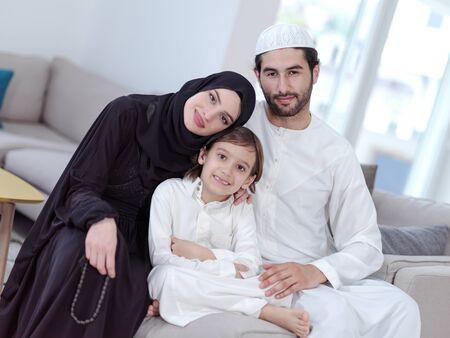 Traditionelle muslimische Familieneltern mit Kindern, die Koran lesen und zusammen auf dem Sofa vor dem Iftar-Abendessen während eines Ramadan-Festes zu Hause beten